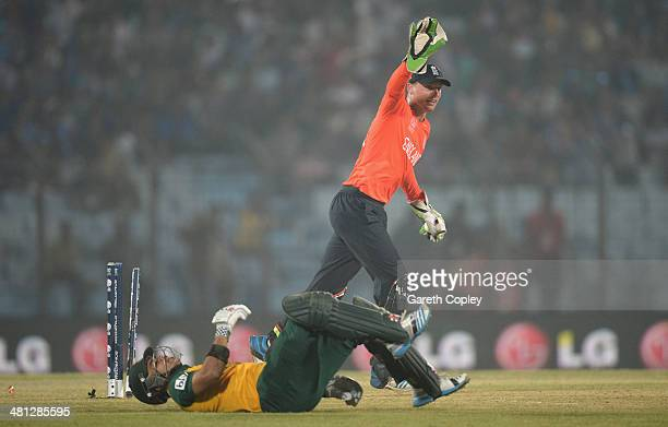 Jos Buttler of England celebrates running out JP Duminy of South Africa during the ICC World Twenty20 Bangladesh 2014 Group 1 match between England...