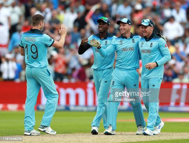 Jos Buttler of England celebrates with team mates Chris Wokes Jofra Archer and Jason Roy after running out Steve Smith during the SemiFinal match of...