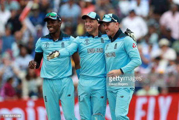 Jos Buttler of England celebrates with team mates Jofra Archer and Jason Roy after running out Steve Smith during the SemiFinal match of the ICC...