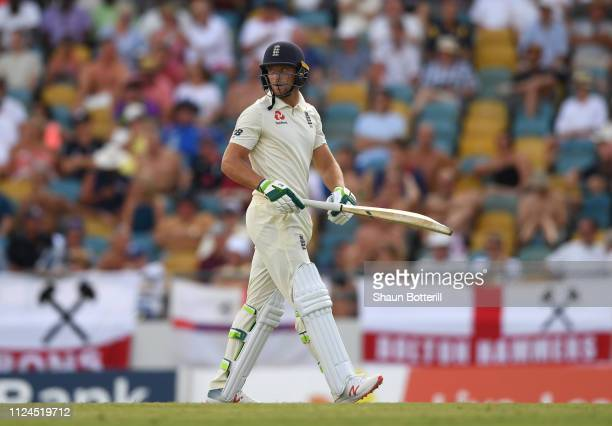 Jos Buttler of England heads back to the pavilion after losing his wicket during Day Two of the First Test match between England and West Indies at...
