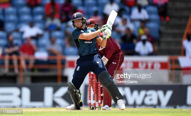 Jos Buttler of England hits out for six runs during the 4th One Day International match between the West Indies and England at Grenada National...