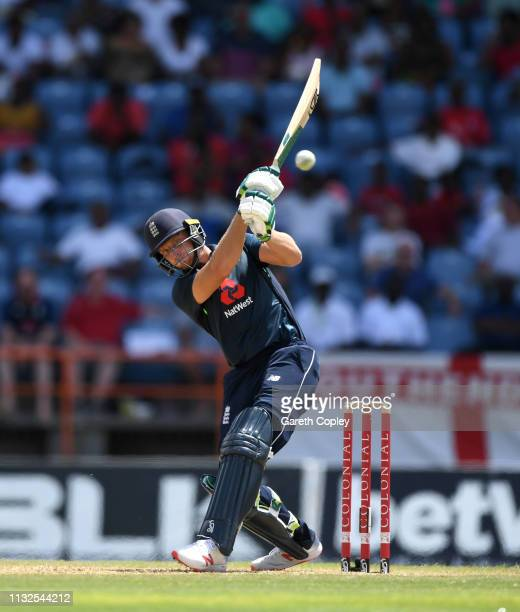 Jos Buttler of England hits ut for six runs during the 4th One Day International match between the West Indies and England at Grenada National...