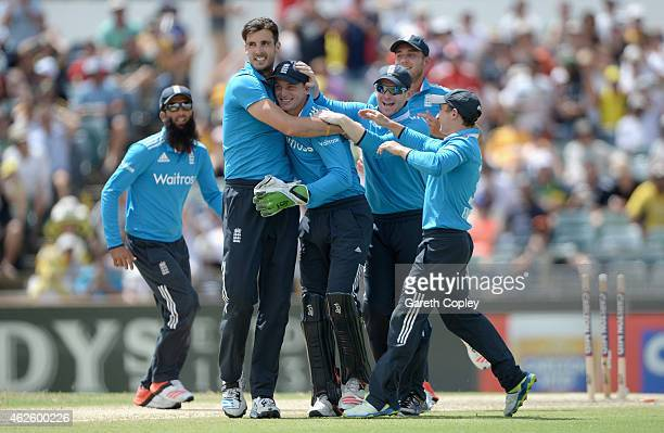 Jos Buttler of England is mobbed by teammates Steven Finn and Eoin Morgan after running out Mitchell Marsh of Australia during the final match of the...