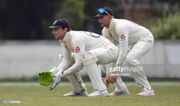 Jos Buttler of England keeps wicket alongside captain Joe Root during day two of the tour match between SLC Board President's XI and England at...