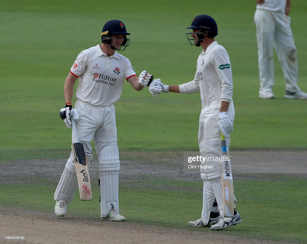 Jos Buttler (L) of Lancashire celebrates with team-mate Tom Bailey after he scores a half century during day two of the Specsavers County Championship division one match between Lancashire and Yorkshire at Emirates Old Trafford on July 23, 2018 in Manchester, England.