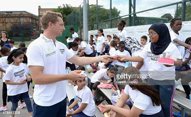 Jos Buttler of Lancashire hands out packets of Switch Hits card game to local school children during an event to celebrate Chance to Shine and...
