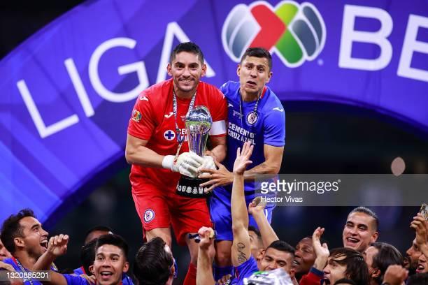 José de Jesús Corona goalkeeper of Cruz Azul and teammate Julio César Domínguez of lift the champions trophy after winning the Final second leg match...