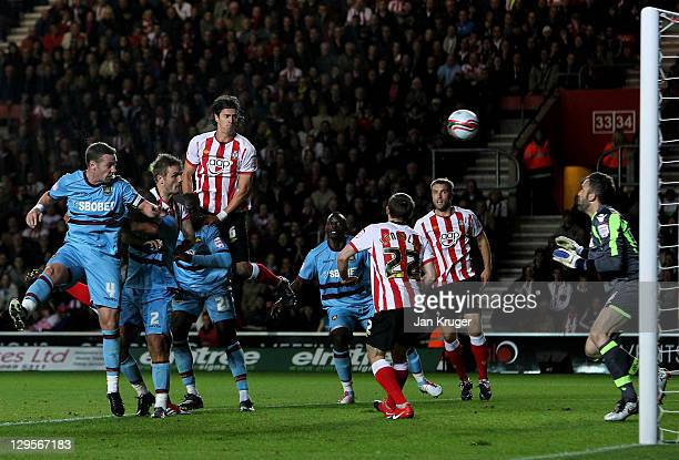 Jos Hooiveld of Southampton heads clear of Manuel Almunia, Goalkeeper of West Ham for the opening goal during the npower Championship match between...