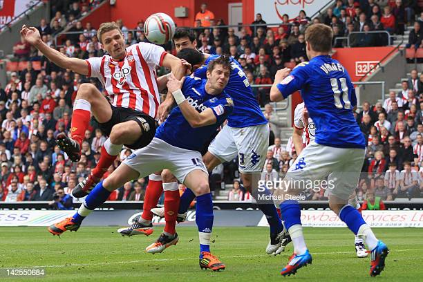 Jos Hooiveld of Southampton heads narrowly wide as Greg Halford of Portsmouth challenges during the npower Championship match between Southampton and...