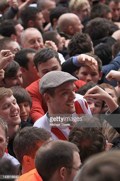 Jos Hooiveld of Southampton sports a flatcap given to him by a home supporter as celebrations begin after Southamptons 40 victory and promotion to...