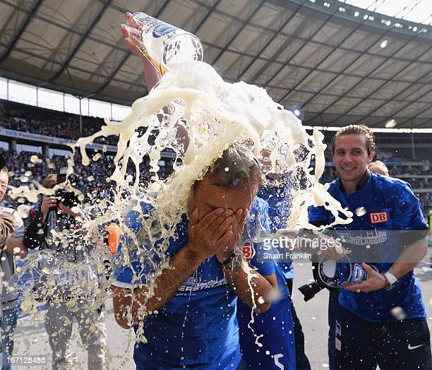 Jos Luhukay head coach of Berlin gets showered in beer as his team celebrates promotion to the first leage at the end of the second Bundesliga match...