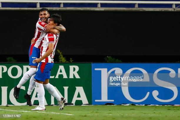 José Macías of Chivas celebrates with his teammates after scoring the first goal of his team during the 9th round match between Chivas and Queretaro...