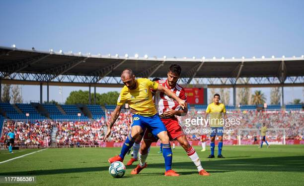 José Romera of UD Almeria competes for the ball with Alberto Perea of Cadiz during the Liga match between UD Almeria and Cadiz at Estadio de los...
