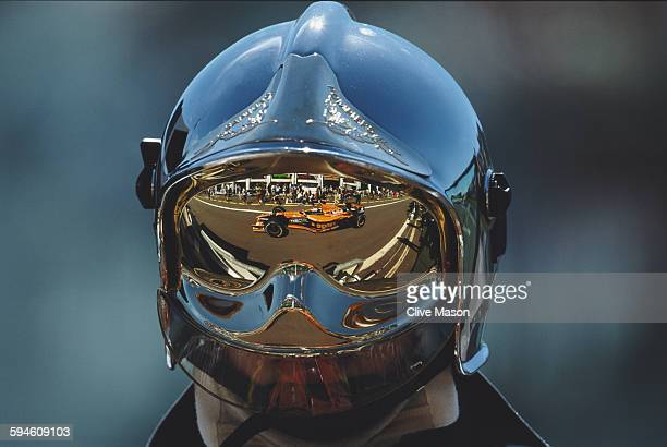 Jos Verstappen of the Netherlands driving the Orange Arrows Asiatech Arrows A22 Asiatech V10 is reflected in the helmet visor of a track fireman...
