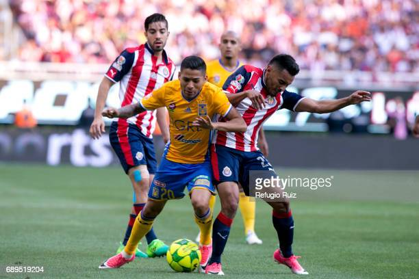 José Vázquez of Chivas fights for the ball with Javier Aquino of Tigres during the Final second leg match between Chivas and Tigres UANL as part of...