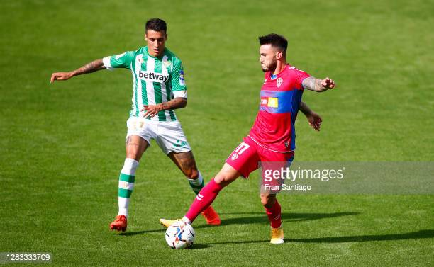 Josan of Elche CF is challenged by Cristian Tello of Real Betis during the La Liga Santander match between Real Betis and Elche CF at Estadio Benito...