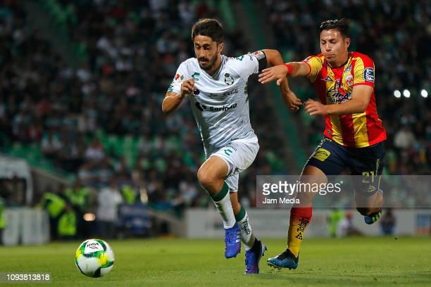 Jose Abella of Santos and Carlos Sebastian Ferreira of Morelia compete for the ball during the 2nd round match between Santos Laguna and Morelia as...