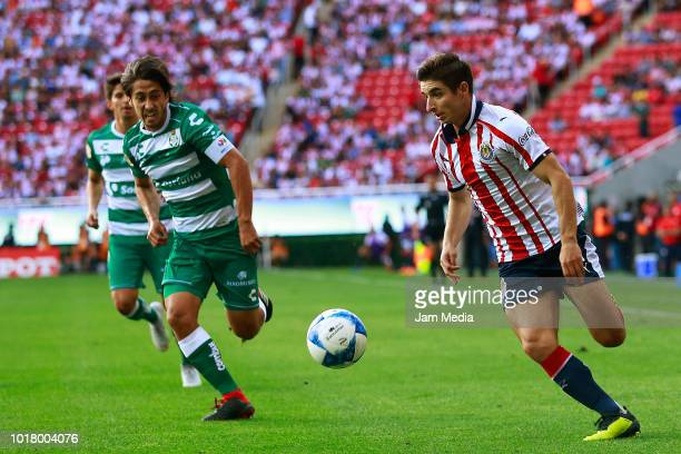Jose Abella of Santos and Isaac Brizuela of Chivas compete for the ball during the fourth round match between Chivas and Santos Laguna as part of the...