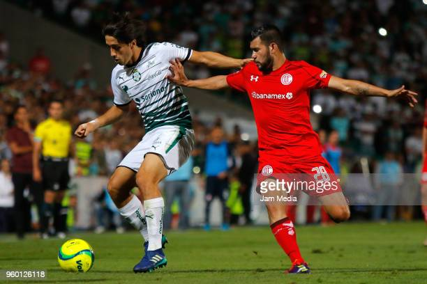 Jose Abella of Santos and Jorge Sartiaguin of Toluca fight for the ball during the Final first leg match between Santos Laguna and Toluca as part of...