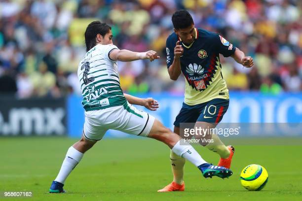 Jose Abella of Santos Laguna struggles for the ball with Cecilio Dominguez of America during the semifinals second leg match between America and...