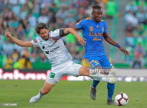 Jose Abella of Santos struggles for the ball with Julian Quinones of Tigres during a semifinal second leg match between Santos Laguna and Tigres UANL...