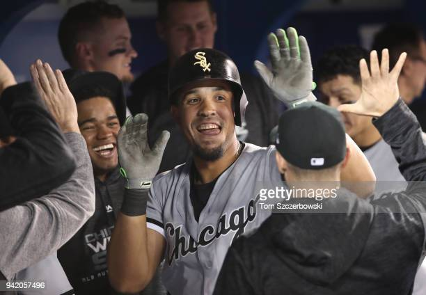 Jose Abreu of the Chicago White Sox is congratulated by teammates in the dugout after hitting a solo home run in the eighth inning during MLB game...