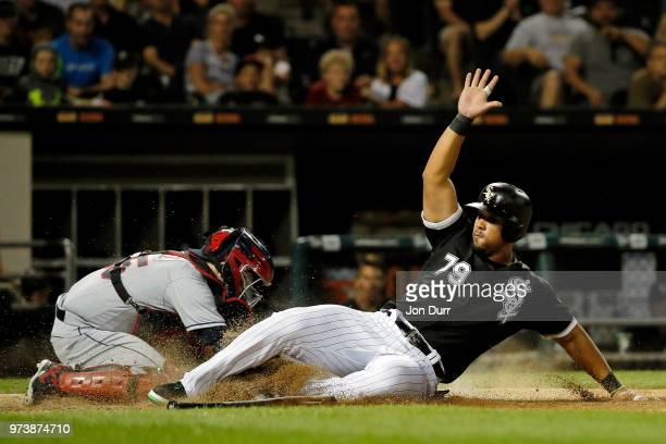 Jose Abreu of the Chicago White Sox slides safely to score on an RBI double hit by Kevan Smith as Roberto Perez of the Cleveland Indians is late with...