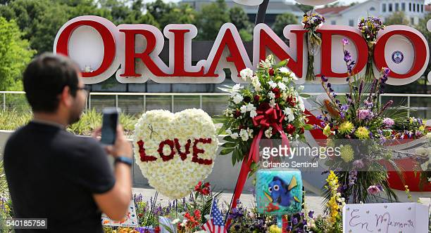 Jose Acevido Negron takes a photo with his iPhone as visitors continue to pay their respects at a makeshift memorial at Orlando Regional Medical...