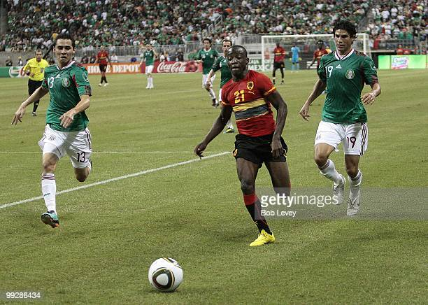 Jose Alberto Mabina of Angola slips past Paul Aguilar and Jonny Magallon of Mexico during the friendly international match between Mexico and Angola...