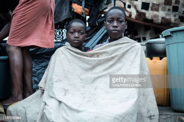 Jose Alberto Simao and Fernando Ali pose as they stay in shelter at the stands of Ring ground in Buzi Mozambiqueon March 23 2019 The death toll in...
