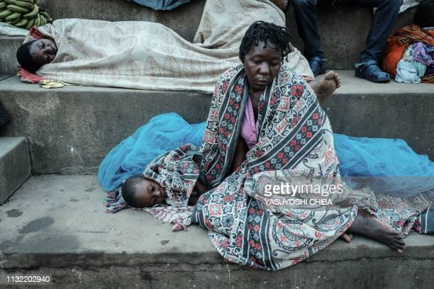 Jose Alberto Simao and Fernando Ali rest as they stay in shelter at the stands of Ring ground in Buzi Mozambique on March 23 2019 The death toll in...