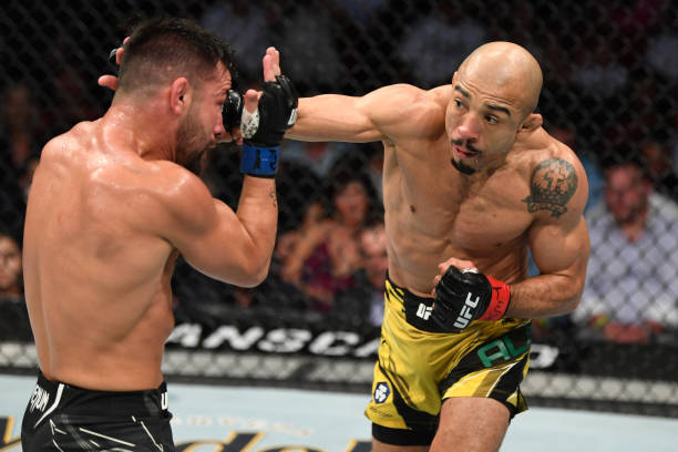 Jose Aldo of Brazil punches Pedro Munhoz of Brazil in their bantamweight bout during the UFC 265 event at Toyota Center on August 07, 2021 in...