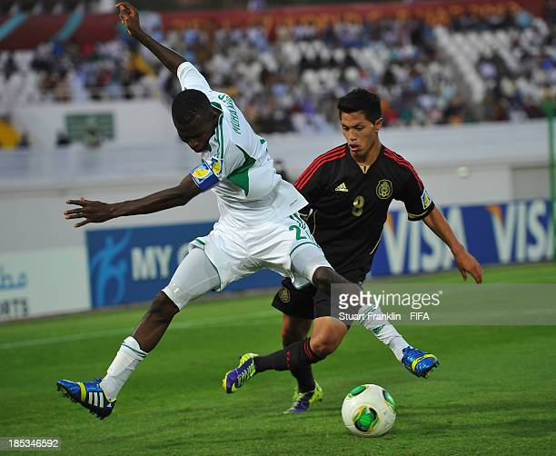 Jose Almanza of Mexico is challenged by Musa Muhammed of Nigeria during the FIFA U17 World Cup group F match between Mexico and Nigeria at Khalifa...