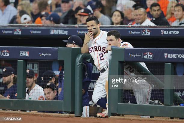 Jose Altuve and Alex Bregman of the Houston Astros look on from the dugout during Game Three of the American League Championship Series against the...