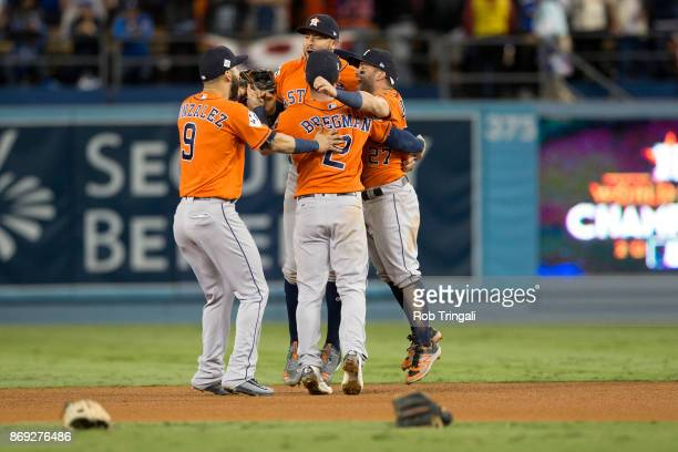 Jose Altuve and Carlos Correa Marwin Gonzalez and Alex Bregman of the Houston Astros celebrate on the field after the Astros defeated the Los Angeles...