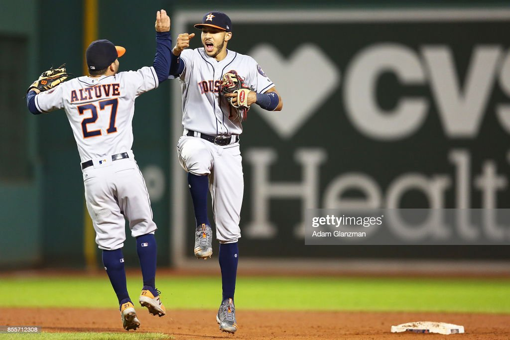 Jose Altuve #27 and Carlos Correa #1 of the Houston Astros celebrate after a victory over the Boston Red Sox at Fenway Park on September 29, 2017 in Boston, Massachusetts.