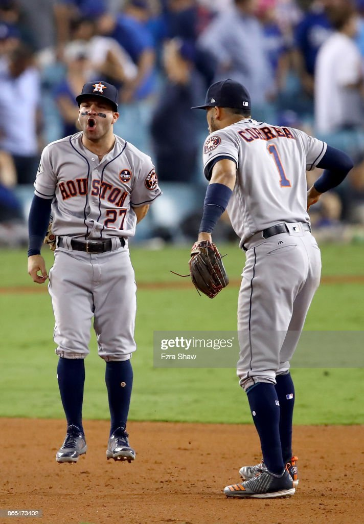 Jose Altuve #27 and Carlos Correa #1 of the Houston Astros celebrate defeating the Los Angeles Dodgers 7-6 in eleven innings to win game two of the 2017 World Series at Dodger Stadium on October 25, 2017 in Los Angeles, California.