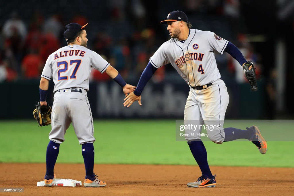 Jose Altuve #27 and George Springer #4 of the Houston Astros celebrate defeating the Los Angeles Angels of Anaheim 1-0 in a game at Angel Stadium of Anaheim on September 12, 2017 in Anaheim, California.