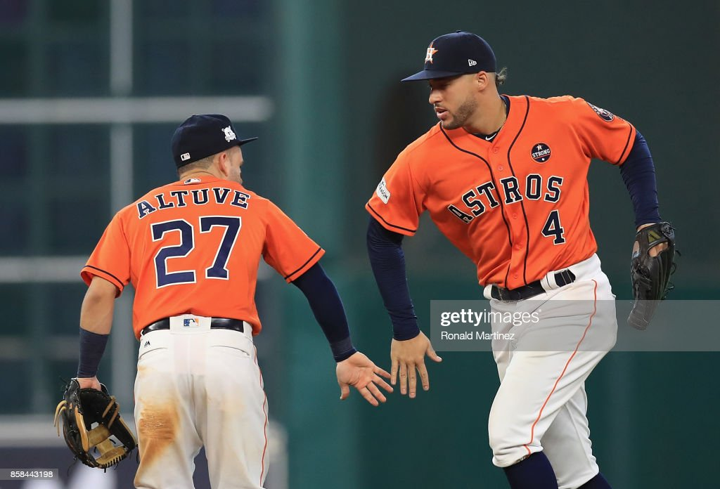 Jose Altuve #27 and George Springer #4 of the Houston Astros celebrate defeating the Boston Red Sox 8-2 in game two of the American League Division Series at Minute Maid Park on October 6, 2017 in Houston, Texas.