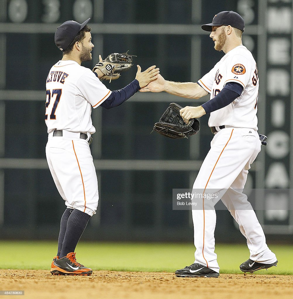 Jose Altuve #27 and Robbie Grossman #19 of the Houston Astros celebrate a win over the Oakland Athletics 4-2 at Minute Maid Park on August 26, 2014 in Houston, Texas.