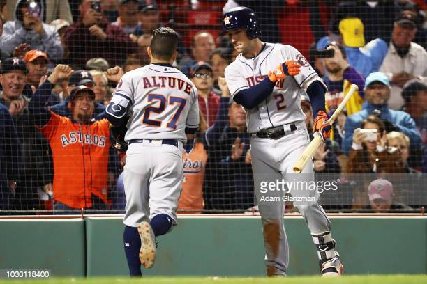 Jose Altuve high fives Alex Bregman of the Houston Astros as he returns to the dugout after hitting a solo home run in the sixth inning of a game...