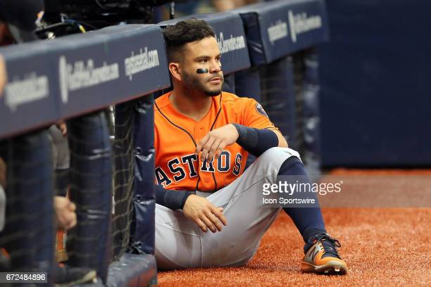 Jose Altuve of the Astros sits near the opening of the dugout and watches the action during the MLB regular season game between the Houston Astros...