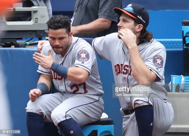 Jose Altuve of the Houston Astros and Jake Marisnick talk as they look on from the top step of the dugout during MLB game action against the Toronto...