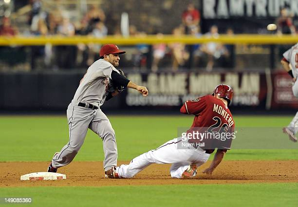 Jose Altuve of the Houston Astros attempts to turn a double play as Miguel Montero of the Arizona Diamondbacks slides into second base at Chase Field...