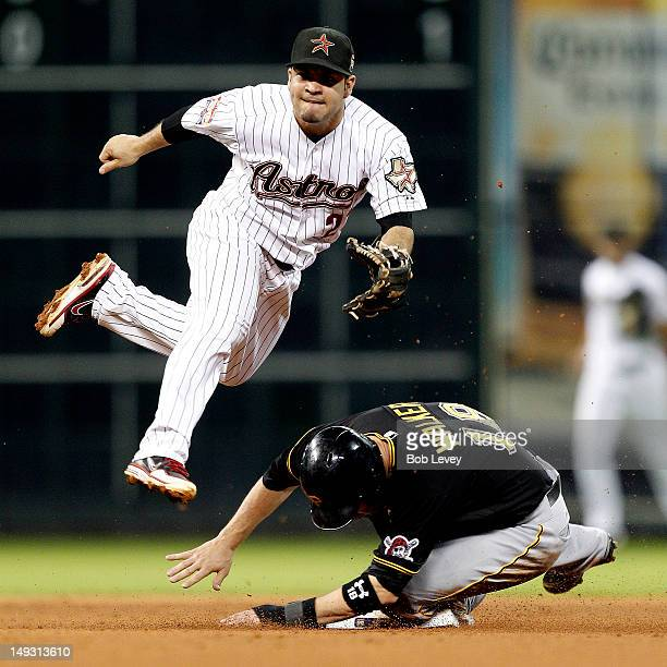 Jose Altuve of the Houston Astros attempts to turn a double play as Neil Walker of the Pittsburgh Pirates slides in at second base at Minute Maid...