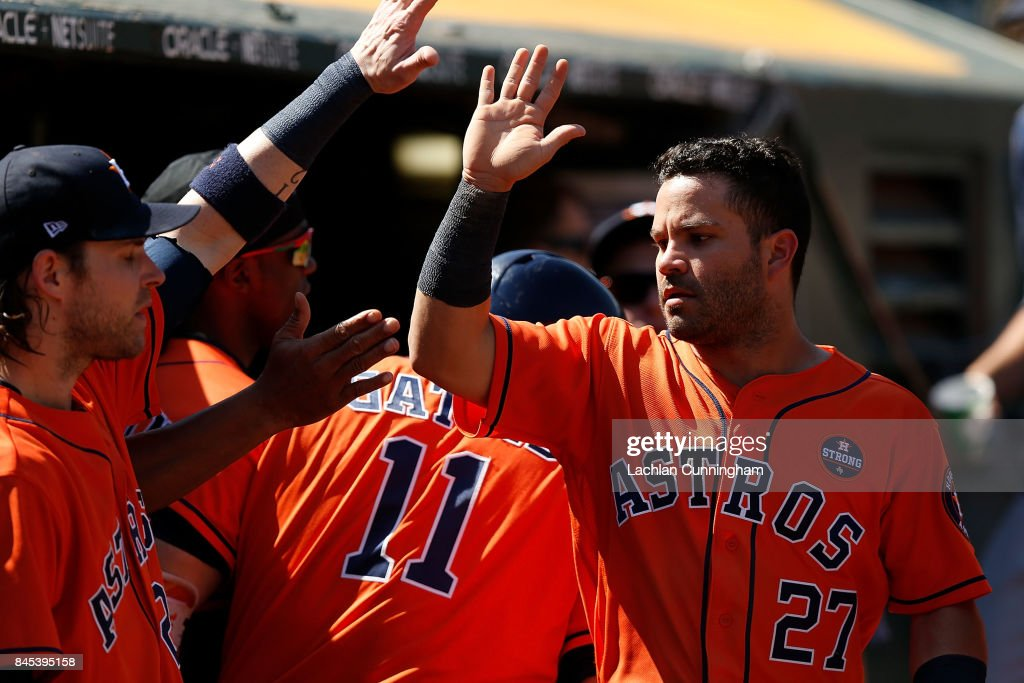 Jose Altuve #27 of the Houston Astros celebrates after scoring on a single hit by Alex Bregman #2 in the sixth inning against the Oakland Athletics at Oakland Alameda Coliseum on September 10, 2017 in Oakland, California.