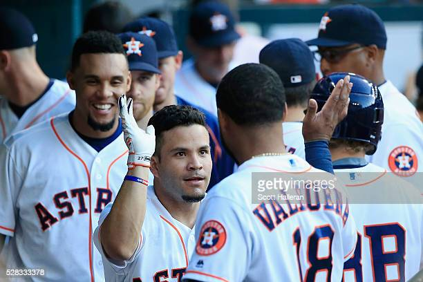 Jose Altuve of the Houston Astros celebrates in the dugout with his teammates after hitting a home run in the first inning off Phil Hughes of the...