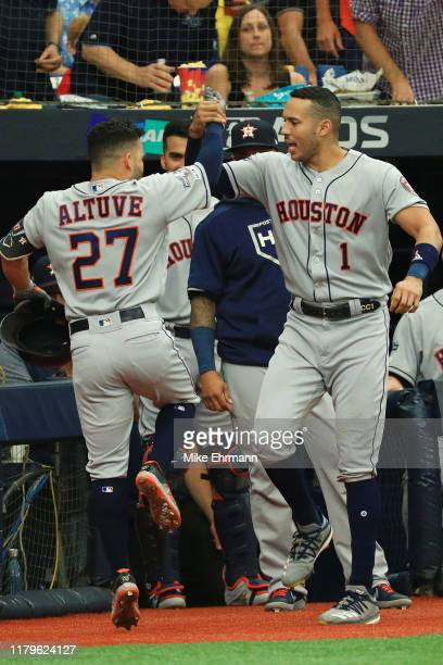 Jose Altuve of the Houston Astros celebrates with Carlos Correa after hitting a solo home run off Charlie Morton of the Tampa Bay Rays during the...