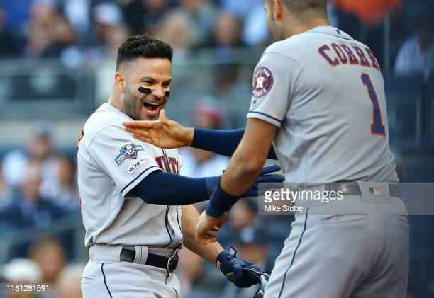 Jose Altuve of the Houston Astros celebrates with Carlos Correa after hitting a solo home run during the first inning against the New York Yankees in...
