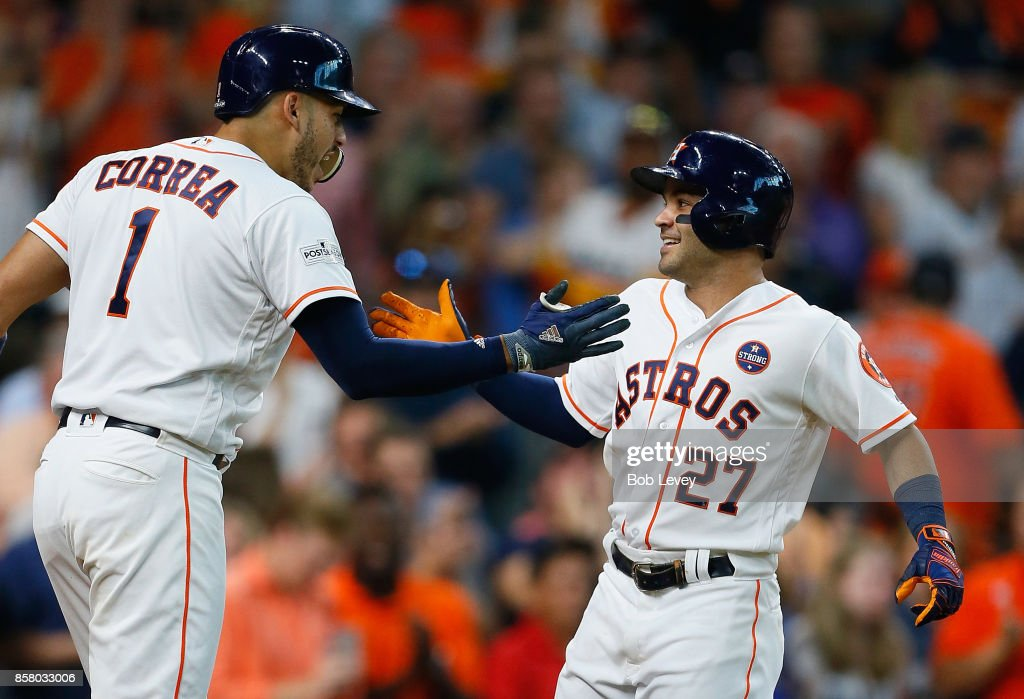 Jose Altuve #27 of the Houston Astros celebrates with Carlos Correa #1 after hitting a home run in the seventh inning against the Boston Red Sox during game one of the American League Division Series at Minute Maid Park on October 5, 2017 in Houston, Texas.